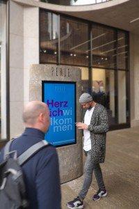 Die Stele begrüsst die Besucher gleich am Eingang der Passage mit plakativen Texten, Angeboten und klassischer Werbung